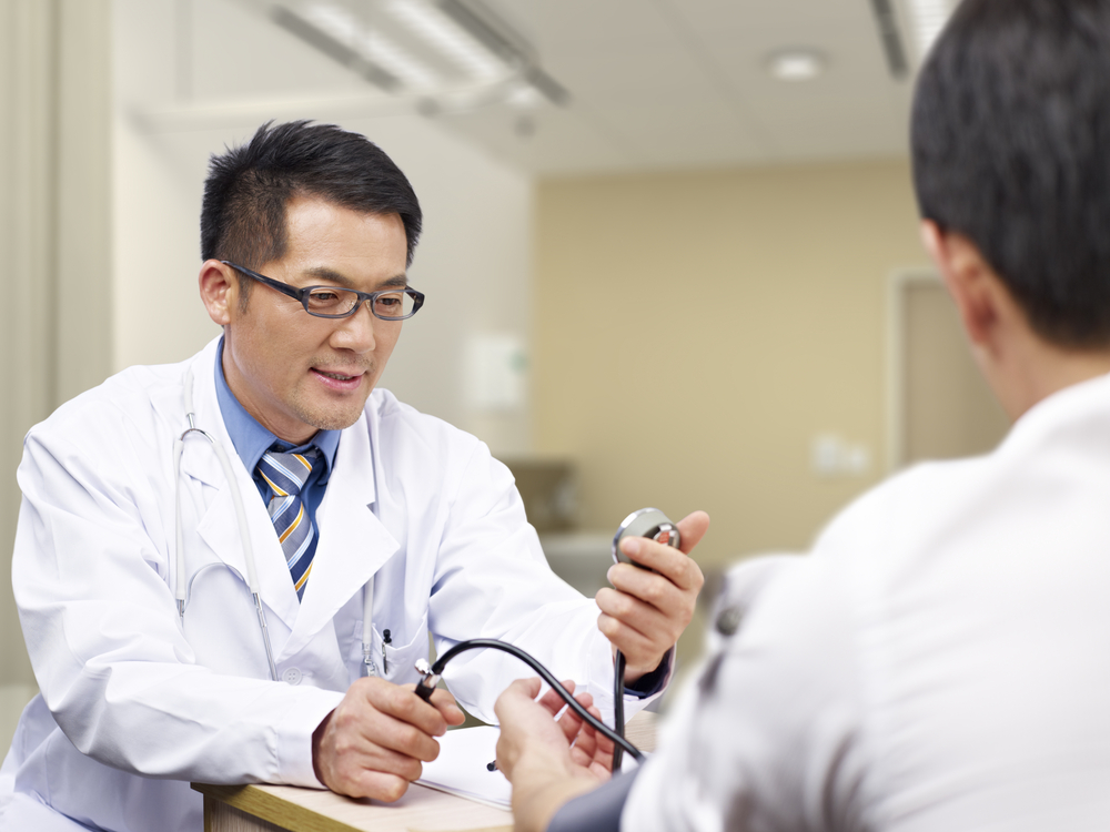 A Doctor looking at a watch in front of a patient, trying to calculate how much time he has left.