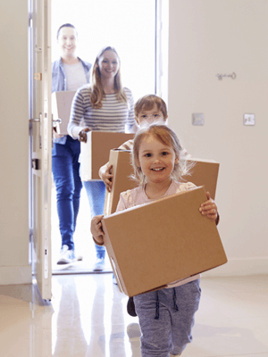 Happy family walking into their new home with boxe