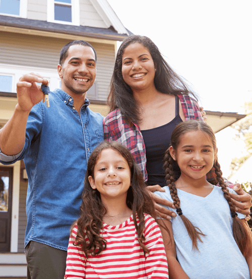 a happy family holding the keys to their new home